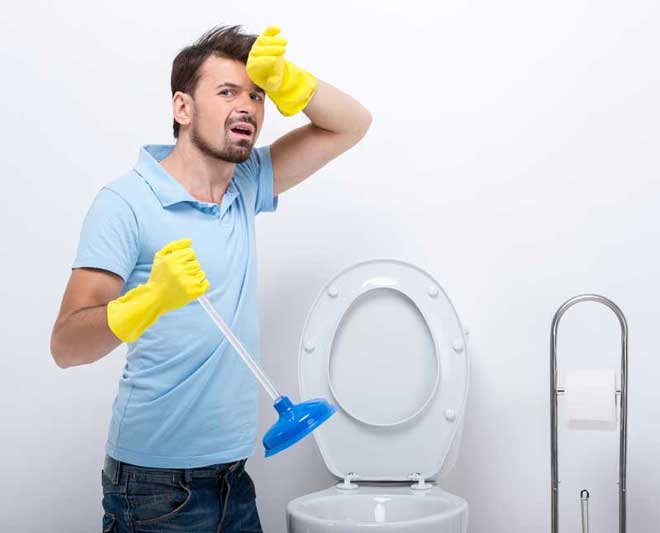 man unclogging his toilet with a plunger